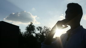 Black Man Talking on Phone, in front of Sun during Sunset, Silhouette stock video