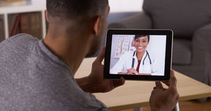 Black man talking to doctor on tablet Stock Photos