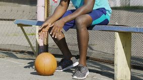 Black man team member bouncing basket ball waiting on the bench, spare player. Stock footage stock footage