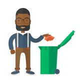 Black man throwing paper in a garbage bin Stock Image
