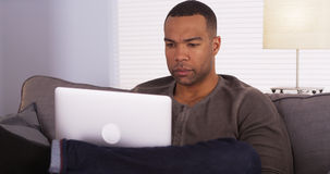 Black man using laptop on couch. Man using laptop on couch Stock Photos