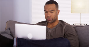 Black man using laptop on couch Stock Photography