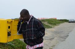 Black Man using Roadside Telephone Stock Images