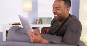 Black man video chatting on tablet smiling. Black man video chatting on tablet stock photo