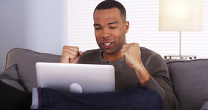 Black man watching the game on his laptop Royalty Free Stock Image