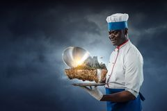 Black man wearing an apron and cooking in action. Mixed media royalty free stock photography