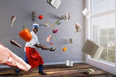 Black man wearing an apron and cooking in action. Mixed media royalty free stock photos