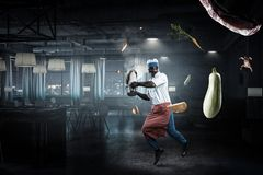 Black man wearing an apron and cooking in action. Mixed media royalty free stock image