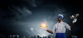 Black man wearing an apron and cooking in action. Mixed media royalty free stock images