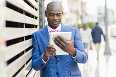 Black man wearing suit and tie looking at his tablet computer. Portrait of black man wearing suit and tie looking at his tablet computer y urban background royalty free stock image