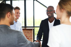 Black man and white man shaking hands. Black men and white men smiling and shaking hands while standing with colleagues Stock Photo