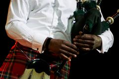 A black man in a white shirt and Scottish kilt holds bagpipes. Multicultural stock photos