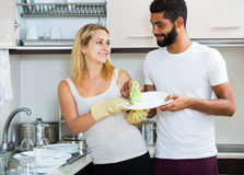 Black man with white woman dusting in domestic kitchen Royalty Free Stock Photography