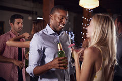 Black man and white woman talking at a party, side view. Black men and white women talking at a party, side view Stock Image
