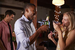 Black man and white woman talking at a party, side view stock photography