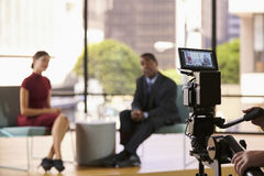 Black man and white woman on TV set, focus on foreground royalty free stock image