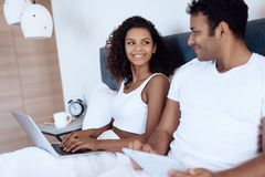 Black man and woman in the bedroom. A woman is working behind a laptop, a man is reading something on his tablet. stock images