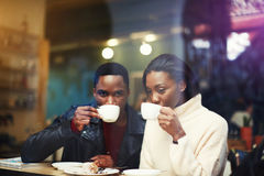 Black man and woman best friends drinking hot cappuccino while get warm together after walking outdoors in cold winter day, Stock Images
