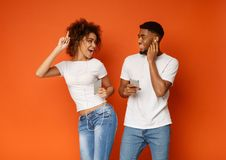 Black man and woman in earphones listening to music on cell phones. Joyful millennial black man and woman in earphones listening to music on cellphones and royalty free stock photo