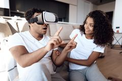 Black man and woman are sitting on the couch. The man put a vr helmet over his head and watches a thrilling film. Royalty Free Stock Images