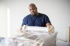 Black man wrapping the furnitures Royalty Free Stock Photo