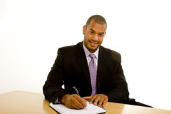 Black Man Writing at Desk and Looking at Camera royalty free stock images