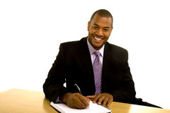 Black Man Writing at Desk and Smiling Stock Photography