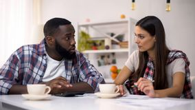 Black man and young lady planning family budget, counting incomes and expenses. Black men and young lady planning family budget, counting incomes and expenses stock photos