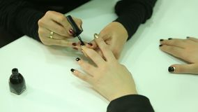 Black manicure. Manicurist does a manicure to the client. Apply gold and black manicure on nails stock video footage