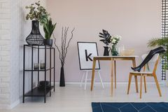 Black mannequin`s leg on wooden chair in elegant dining room interior with copy space on the empty wall, flowers and leaf in vase. S on the floor and poster on stock photo