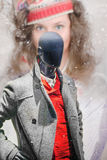 Black mannequin with winter clothes and a blurry girl`s face in Royalty Free Stock Image