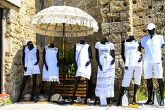 Black mannequins with a white summer line of resort clothing are standing under a beautiful umbrella near a store stock photography