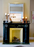 Black mantle with mirror & candlesticks. Fireplace with logs Stock Photography