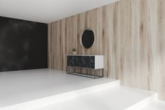 Black marble chest of drawers, mirrors. Black marble chest of drawers standing in a black marble and a wooden wall living room with a concrete floor and a round Stock Photo