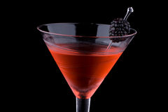 Black martini - Most popular cocktails series. Martini in chilled glass over black background on reflection surface. Red color, made with blackberry liqueur and Stock Photography