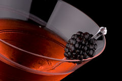 Black martini - Most popular cocktails series. Martini in chilled glass over black background on reflection surface. Red color, made with blackberry liqueur and Royalty Free Stock Image