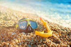The black mask for diving and the tube lie on the beach, on the sand. The concept of tourism and travel. Stock Photos