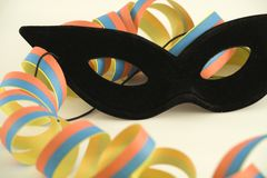 Black mask and streamer. A black Mardi Gras mask and a streamer in detailed view. No extra sharpening, selective focus on mask Royalty Free Stock Photography
