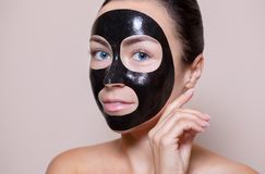 Black mask on the face of a beautiful woman. Spa treatments and skin care in the beauty salon. Royalty Free Stock Images