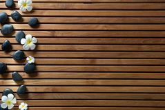 Black massage pebbles and spa flowers set on wooden board Royalty Free Stock Image