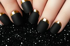 Black matte nail polish. Manicured nail with black matte nail po. Lish. Manicure with dark nailpolish. Golden nail art manicure Royalty Free Stock Photos