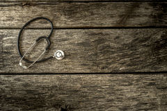 Black medical stethoscope lying on aged textured wooden planks Royalty Free Stock Images