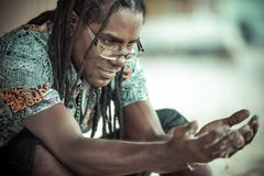 Black men with dreadlocks thinking about the transience of time. Сonceptual portrait of black man with dreadlocks Royalty Free Stock Photos