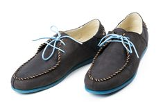 Black men's leather loafers with blue soles and laces on a white Stock Image