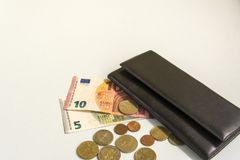 Black men`s purse. Banknotes in five and ten euros. Several coins. On beige background stock images