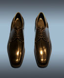 Black Men's Shoes Isolated on Blue Royalty Free Stock Image