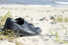 Black men's shoes standing on the sandy beach, vacation background Royalty Free Stock Photography