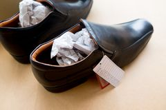The black men`s shoes. With tag price and size Stock Image