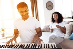 A black man sits in the living room of his apartment and plays synthesizer. A girl sitting next to him and drinking tea. A black men sits in the living room of stock photo
