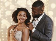 Man in suit putting golden chain on happy lady neck